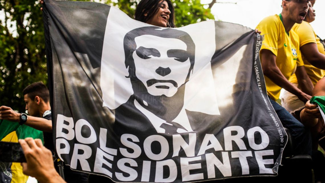 Supporters of Brazilian right-wing presidential candidate Jair Bolsonaro gather with a flag outside an Air Force base in downtown Rio de Janeiro.