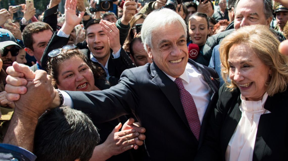 Chilean President Sebastián Piñera (centre) and his wife Cecilia Morel (right) celebrate after the decision of the International Court of Justice regarding Bolivia's maritime claim against Chile at La Moneda presidential palace in Santiago.