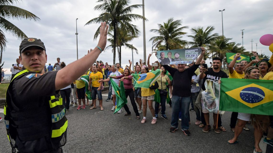 A Brazilian policeman tries to hold back supporters of Brazilian right-wing presidential candidate Jair Bolsonaro that gather outside his house in Barra Da Tijuca, Rio de Janeiro, Brazil on September 29, 2018, after his arrival from Sao Paulo where he was discharged from the Israelita Albert Einstein Hospital, where he remained the last weeks after he was stabbed on September 6 during a campaign rally in the southern state of Minas Gerais. As detractors organize marches across Brazil against the 63-year-old former army captain who has been branded racist, misogynist and homophobic, under the hashtag #EleNao (Not Him), his supporters also take to the streets and laud his tough stance on tackling Brazil's rising crime rate and his pledge to protect traditional family values.