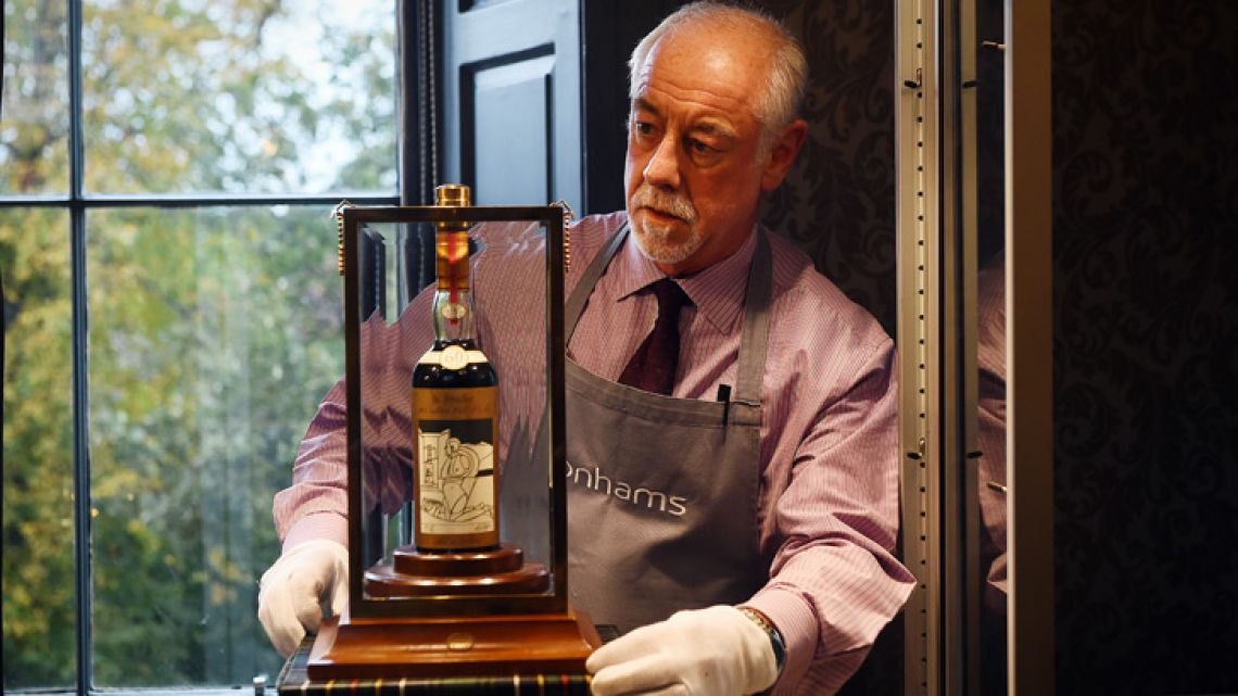 A Bonhams porter shows the bottle of Macallan Valerio Adamai 1926 whiskey which sold for a world record sale price of £700,000 at auction in Edinburgh on October 3, 2018. The whiskey, which was in a vat for 60 years from 1926 then bottled, fetched £700,000 plus a £148,000 sales premium to make it the most expensive whisky for £848,000.