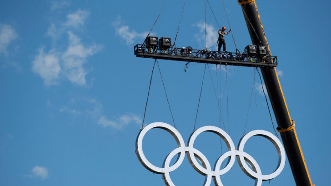 The Olympic Rings are craned into position at the Obelisk, ahead of Saturday's opening ceremony for the Youth Olympic Games.