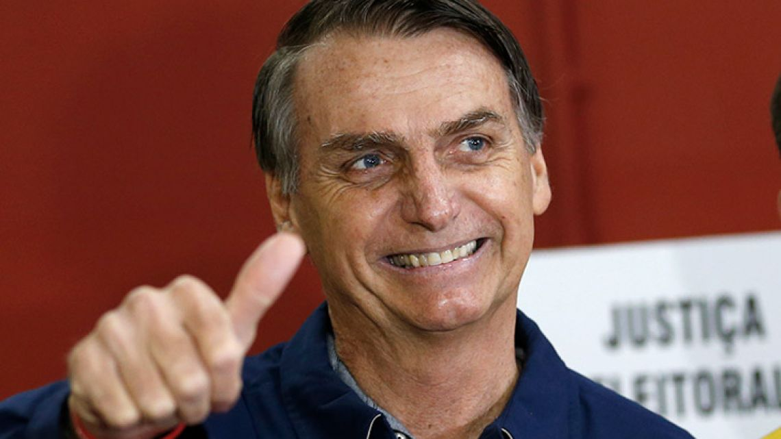 Jair Bolsonaro, of the Social Liberal Party, left, flashes a thumbs up at a polling station in Rio de Janeiro, Brazil, Sunday.