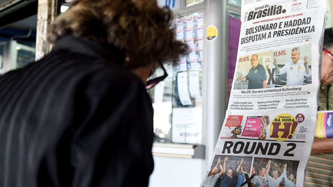 A woman reads the front page of a newspaper referring to the results of the first round national election at a newsstand in Brasilia.