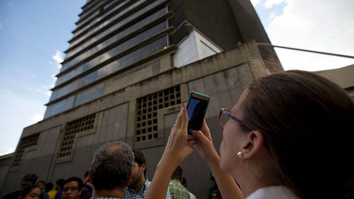 "Manuela Bolívar, a lawmaker and member of the Primera Justicia (""Justice First"") party, takes photos of the Bolivarian National Security Service (SEBIN) headquarters in Caracas, Venezuela, on Monday. Venezuela's Attorney General Tarek William Saab said Monday that councilman Fernando Alberto Alban Salazar, who was arrested on suspicion of involvement in a failed assassination attempt on President Nicolás Maduro, has died of suicide while jailed at SEBIN."
