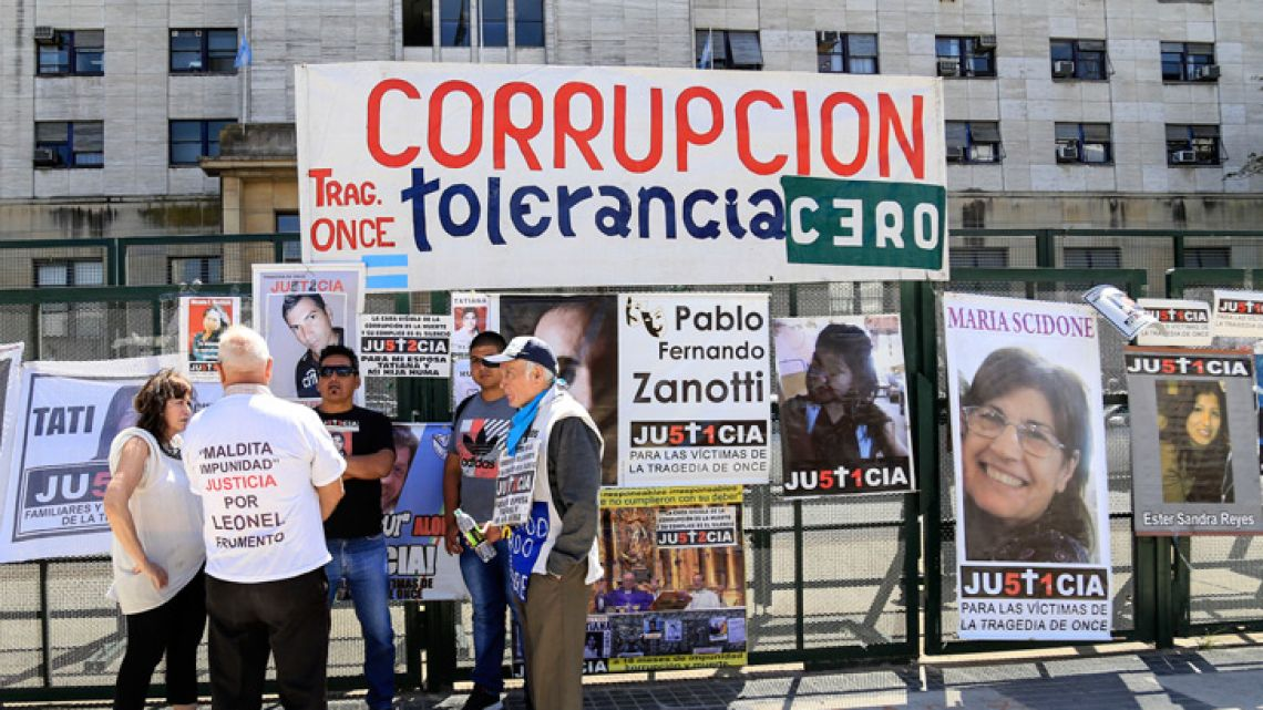 Families of the victims of the Once train tragedy gather in front of the Comodoro Py courthouse, as they await sentencing in the case.