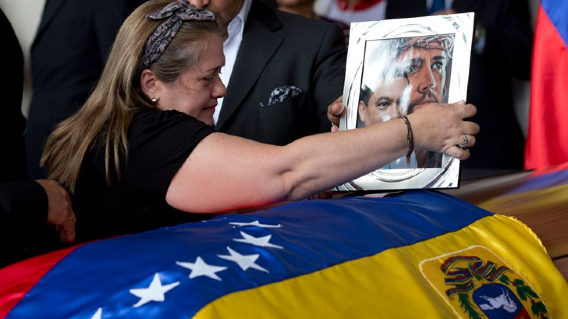 Luz Alban, the sister of opposition activist Fernando Alban places a framed portrait of her brother during a solemn ceremony at the National Assembly headquarters, in Caracas, Venezuela