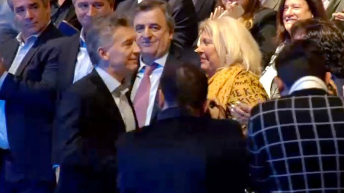 Macri and Carrio and an awkward salute.