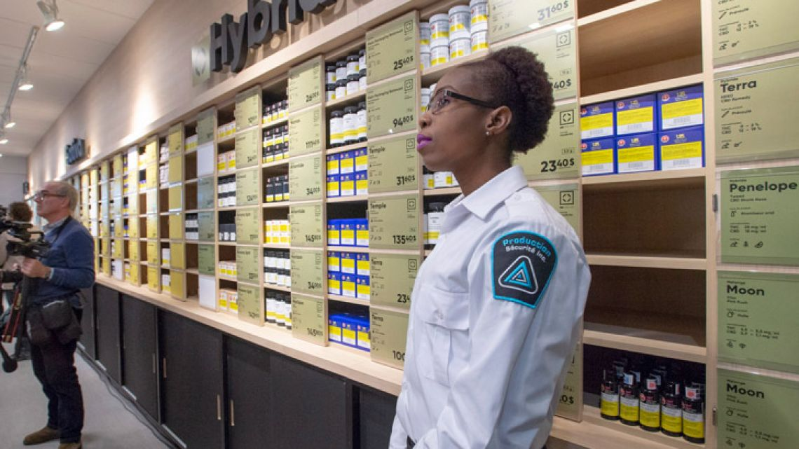 A security guard keeps an eye on reporters and photographers at a new Societe Quebecoise du Cannabis (SQDC) store during a media preview Tuesday, Oct. 16, 2018 in Montreal.