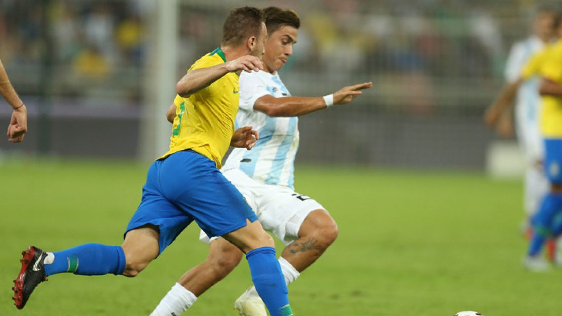 Argentina's forward Paulo Dybala (right) drives the ball forward during the friendly football match Brazil vs Argentina at the King Abdullah Sport City Stadium in Jeddah on October 16, 2018.