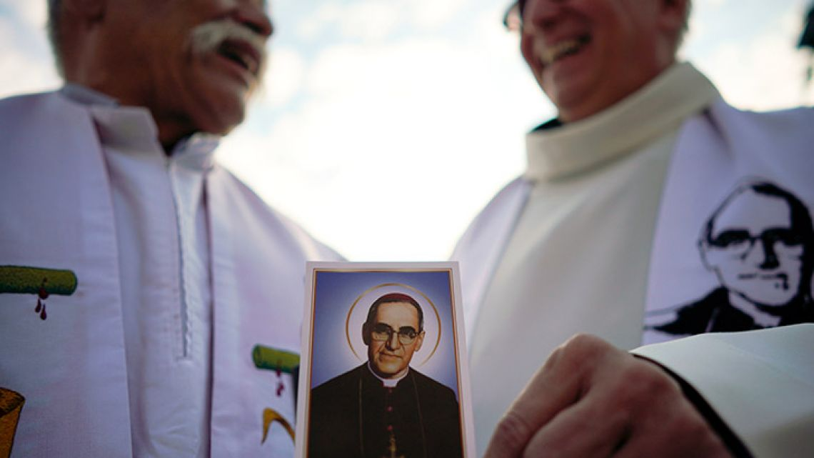 A priest holds a picture of martyred Salvadoran archbishop Óscar Romero prior to a canonisation ceremony in St. Peter's Square at the Vatican.