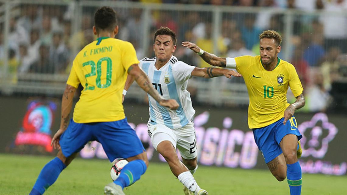Brazil's forward Neymar (right) fights for the ball with Argentina's forward Paulo Dybala (left) during the friendly match at the King Abdullah Sport City Stadium in Jeddah on October 16, 2018.