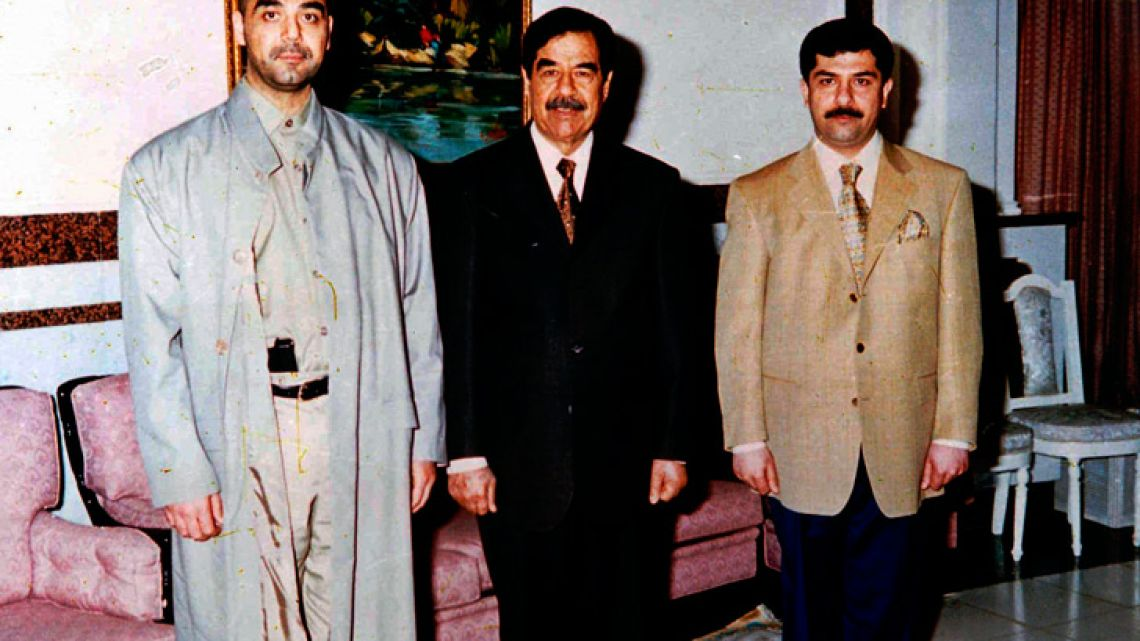 Iraqi ruler Saddam Hussein poses with his two sons Oday, left, and Qusay.