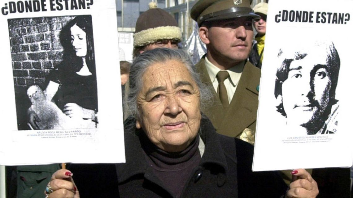 In this July 6, 2002 file photo, Ana González with photos of four of her relatives who were disappeared during the military dictatorship, participates in a protest march in Santiago, Chile. González, one of Chile's leading human rights advocates has died on Friday, Oct. 26, 2018, without knowing the fate of her husband, two children and pregnant daughter-in-law, who were forcibly disappeared during the country's dictatorship.