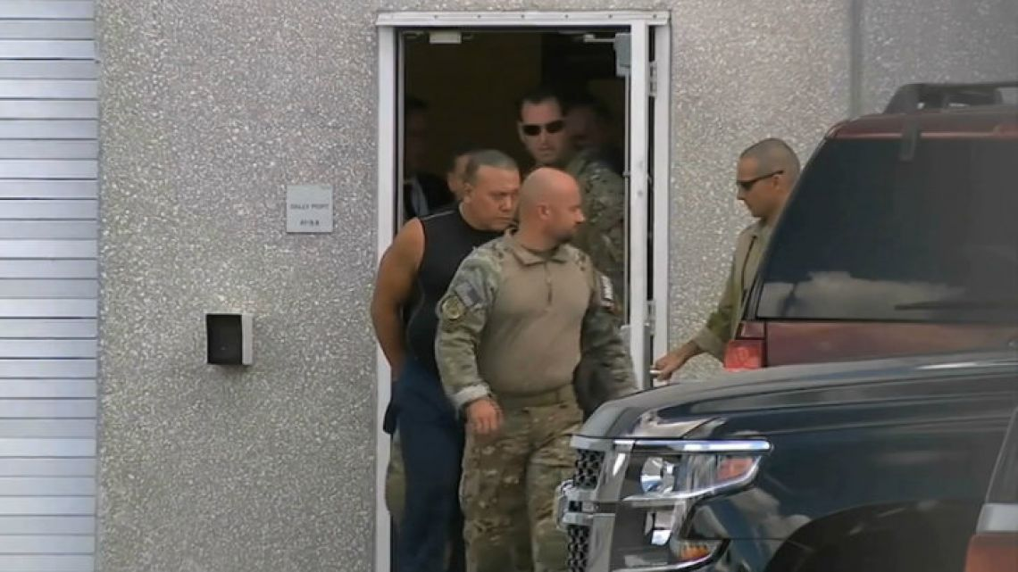 FBI agents escort Cesar Sayoc, in sleeveless shirt, into custody.
