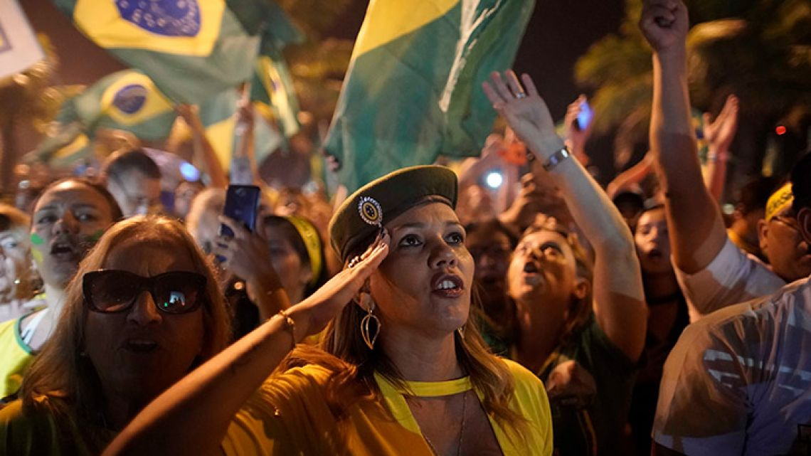A supporter of Jair Bolsonaro salutes during a celebration in front of his residence after he was declared the winner of Brazil's election run-off, in Rio de Janeiro.