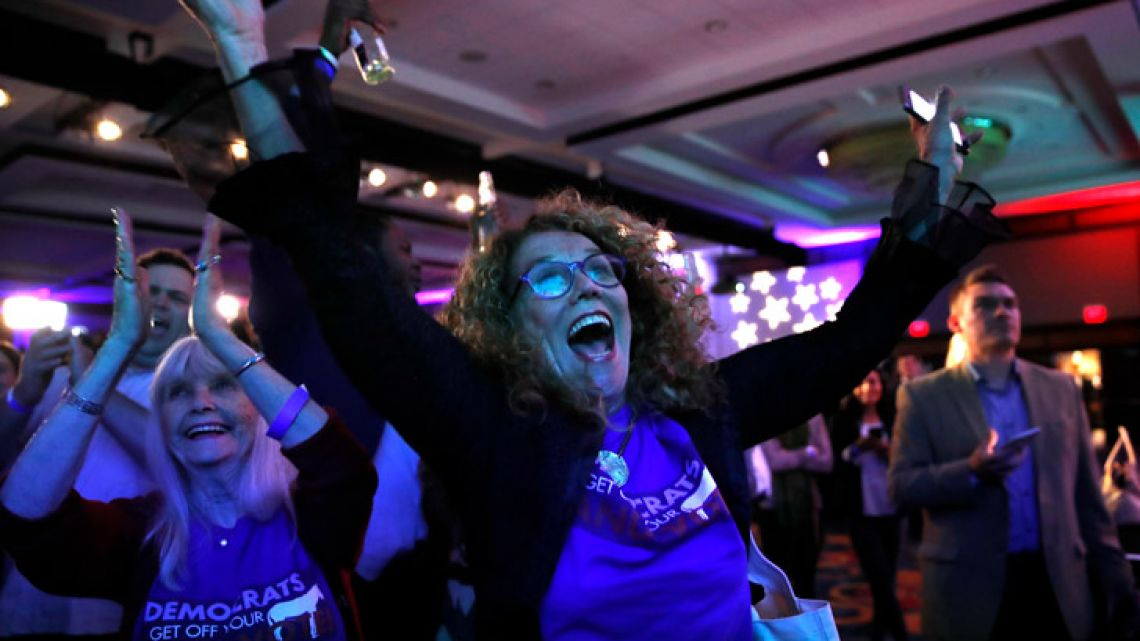 Sydney Crawford, 84, left, of New York City, and JoAnn Loulan, 70, of Portola Valley, Calif., watch election returns during a Democratic party election night event Tuesday at the Hyatt Regency Hotel, in Washington.