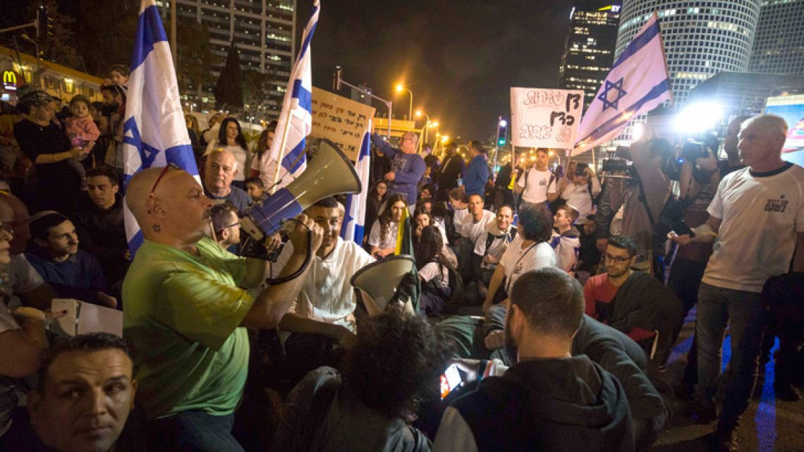 Israeli protesters hold flags and chant slogans during a demonstration against the ceasefire between Israel and Gaza's Hamas in Tel Aviv on Thursday night.