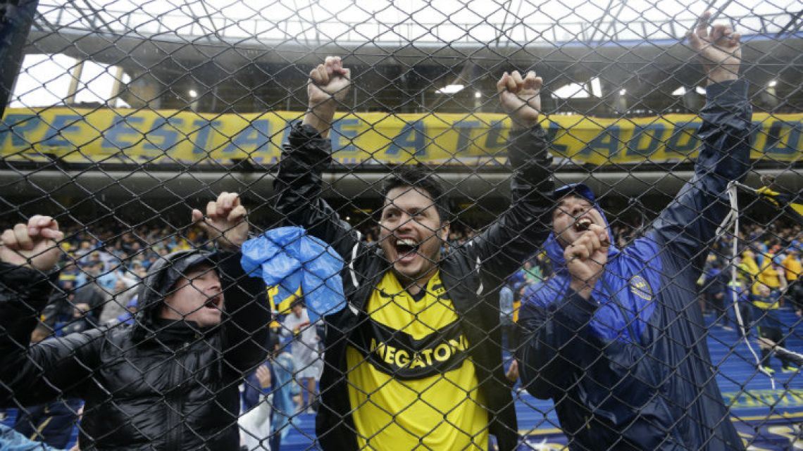 Boca Juniors fans cheer under the rain, from the stands of the Bombonera, ahead of last Saturday's match with River Plate.