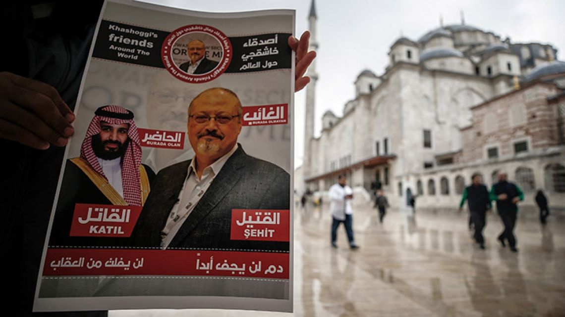 """A man holds a poster showing images of Saudi Crown Prince Muhammed bin Salman and of journalist writer Jamal Khashoggi, describing the prince as """"assassin"""" and Khashoggi as """"martyr"""" during funeral prayers in absentia for Khashoggi who was killed last month in the Saudi Arabia consulate, in Istanbul, Friday, Nov. 16, 2018. Turkey's Foreign Minister Mevlut Cavusoglu on Thursday called for an international investigation into the killing of the Saudi dissident writer Jamal Khashoggi."""