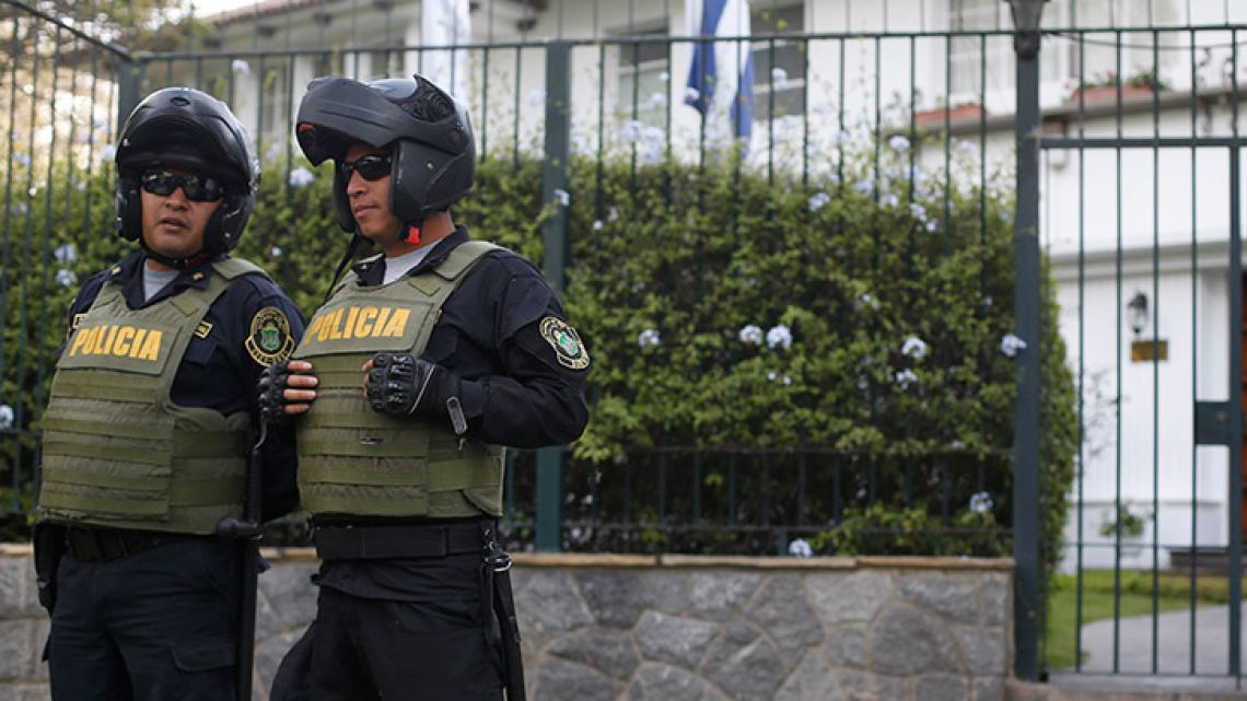 Police stand outside the residence of Uruguay's ambassador to Peru, in Lima. Former Peru president Alan García has sought asylum in Uruguay's diplomatic mission hours after a judge retained his passport as part of a corruption probe, Peru's Foreign Ministry has announced.