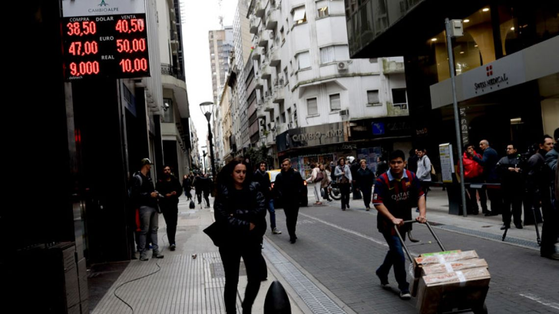 People walk past an exchange house in Buenos Aires, Argentina.