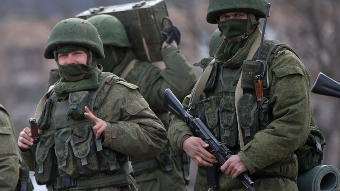 A pro-Russian soldier flashes a victory sign while marching near a Ukrainian army base in March 2014 in Perevalne, Crimea.