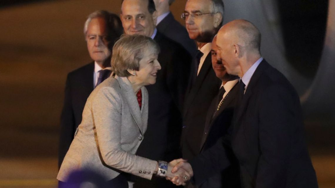 Britain's Prime Minister Theresa May greets UK Ambassador to Argentina Mark Kent upon her arrival to the Ministro Pistarini international airport in Buenos Aires, Argentina.