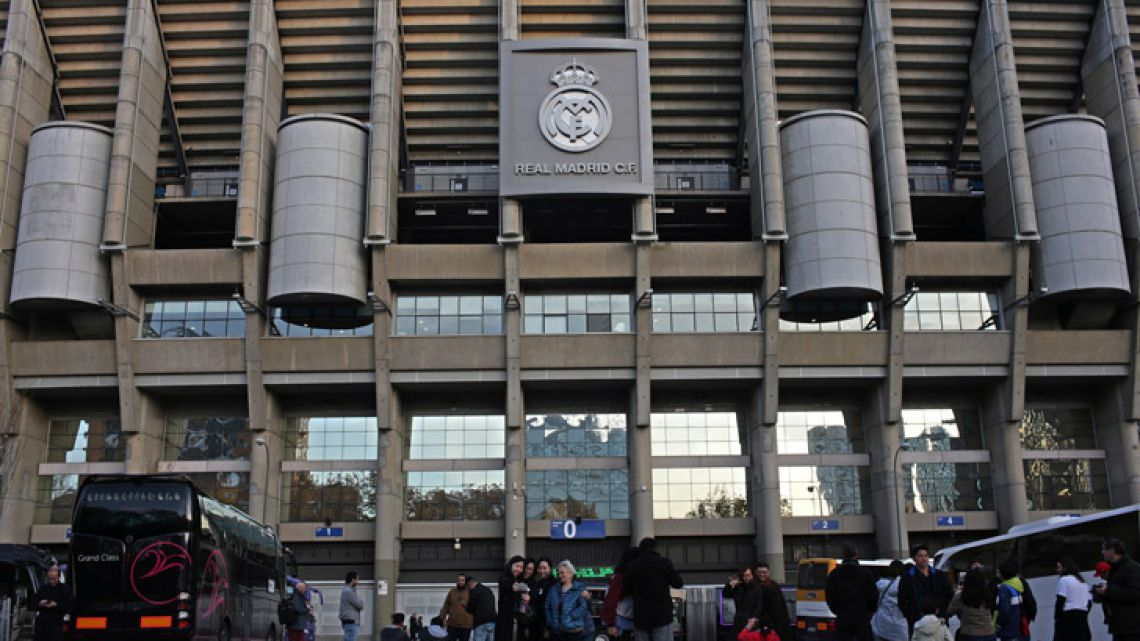 People stop to take pictures in front of Real Madrid's Santiago Bernanabeu stadium in Madrid on Dec. 7, 2018.