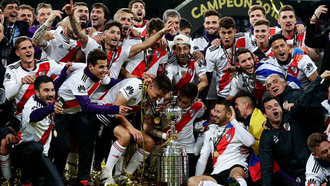 River Plate's players celebrate with the Copa Libertadores trophy, after beating arch-rivals Boca Juniors in Madrid.