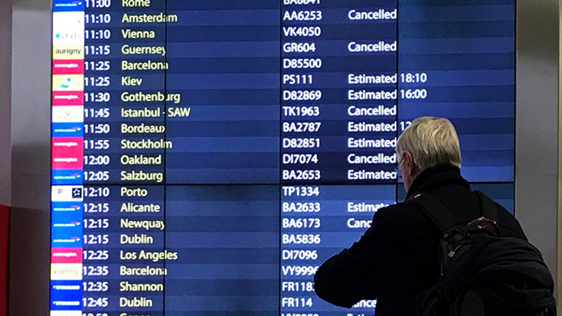 A passenger checks an arrivals board at Gatwick Airport in England, Friday, Dec. 21, 2018.