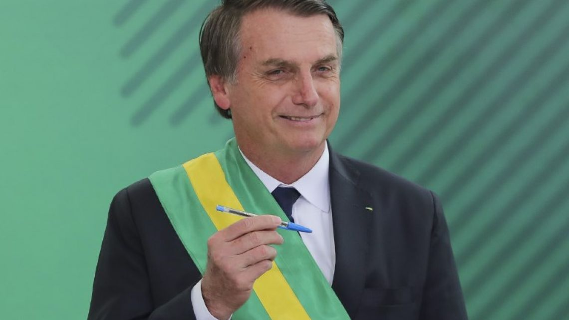 Brazil's new President Jair Bolsonaro poses with the pen used during the swearing-in ceremony for the ministers at the Planalto Palace in Brasilia on January 1, 2019.