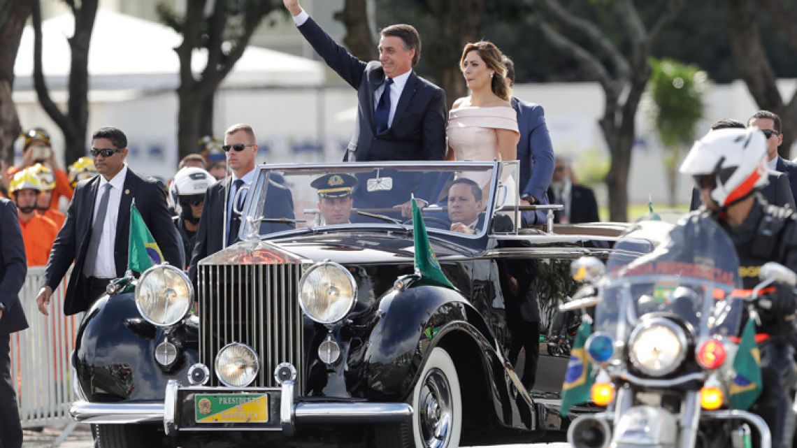 Flanked by First Lady Michelle Bolsonaro, Brazil's President Jair Bolsonaro waves as he rides in an open car after his swearing-in ceremony in Brasilia on January 1.