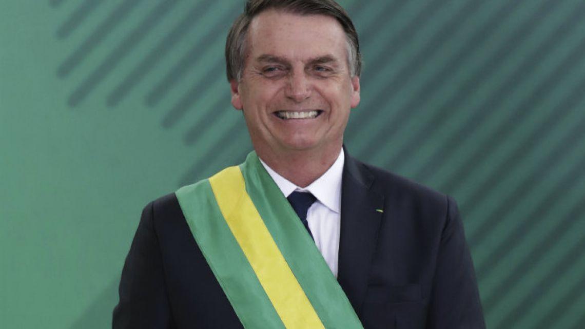 Brazil's President Jair Bolsonaro smiles during a Cabinet meeing in Brasilia.