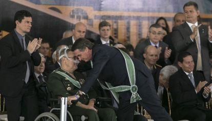 Acto. Bolsonaro abraza a Eduardo Villas Bôas, ante la atenta mirada del ministro Sérgio Moro.