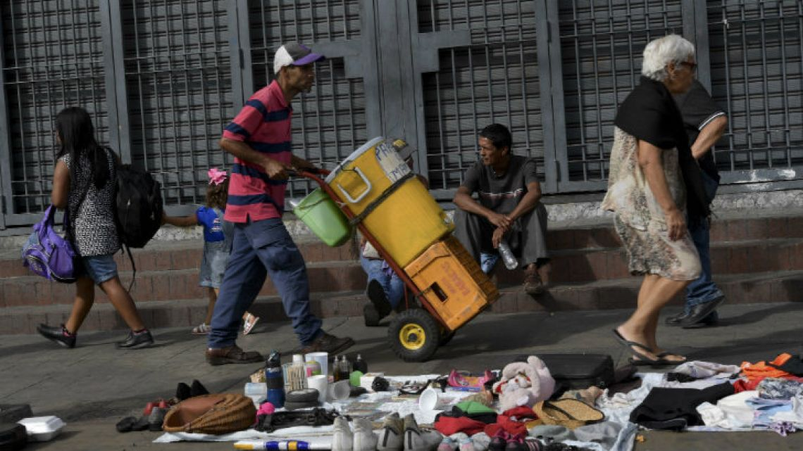 Pedestrians walk in front of second-hand clothes, shoes, and other goods for sale or exchange in Caracas.