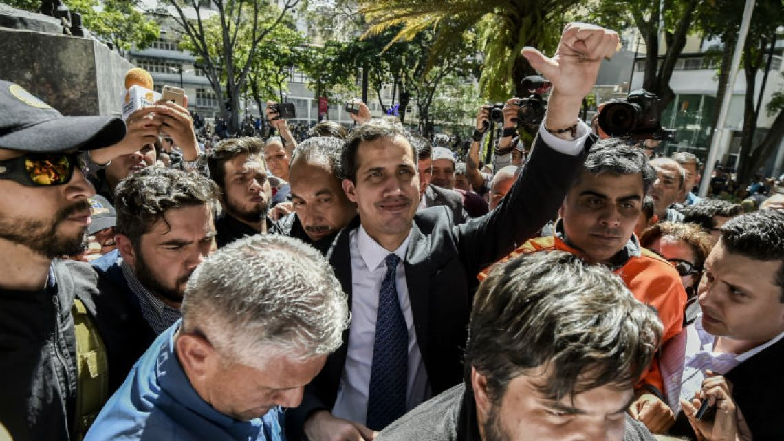 "Venezuela's National Assembly speaker and the country's self-proclaimed ""acting president"" Juan Guaidó waves to supporters in Chacao yesterday."