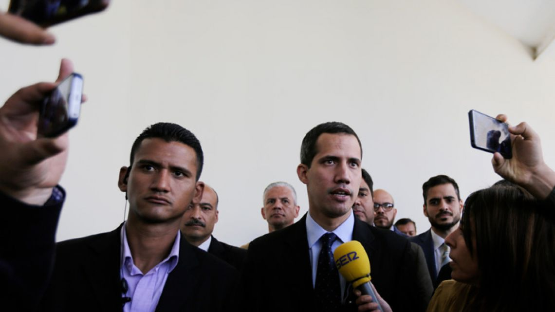 National Assembly President Juan Guaidó, who declared himself interim president of Venezuela, speaks with the media upon his arrival to National Assembly in Caracas, Venezuela on Tuesday.