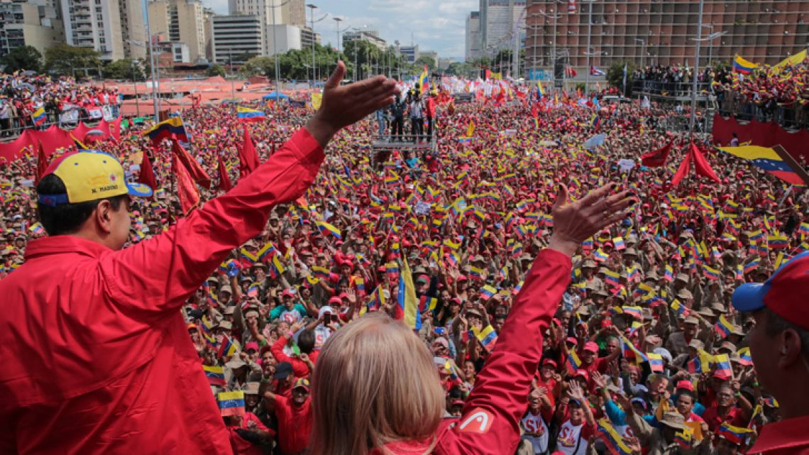 Handout picture released by the Venezuelan presidency showing Venezuelan President Nicolás Maduro (left) and his wife Cilia Flores wave at the crowd during a gathering to mark the 20th anniversary of the rise of power of the late Hugo Chávez.