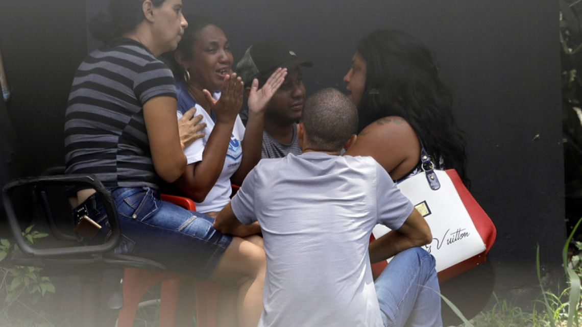Relatives cry as they await news after a deadly fire at the academy of the Flamengo football club in Rio de Janeiro, Brazil.