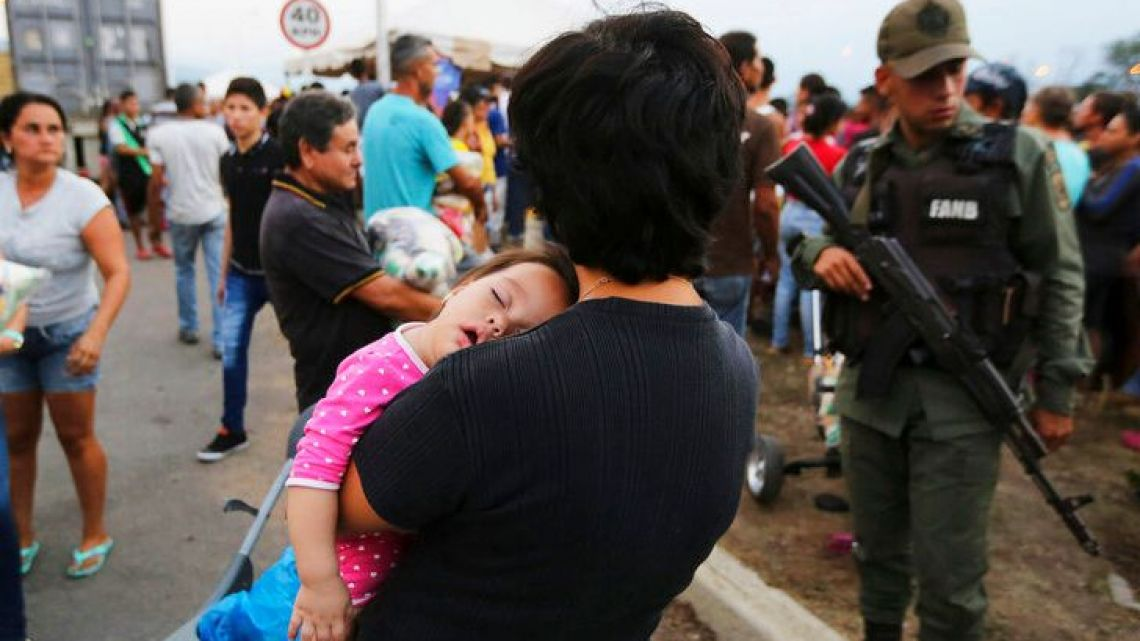 A woman carries her baby as she was waiting for her husband was trying to get a bag with food subsidized by the Nicolas Maduro's government near the international bridge of Tienditas on the outskirts of Urena, Venezuela, in February 2019.