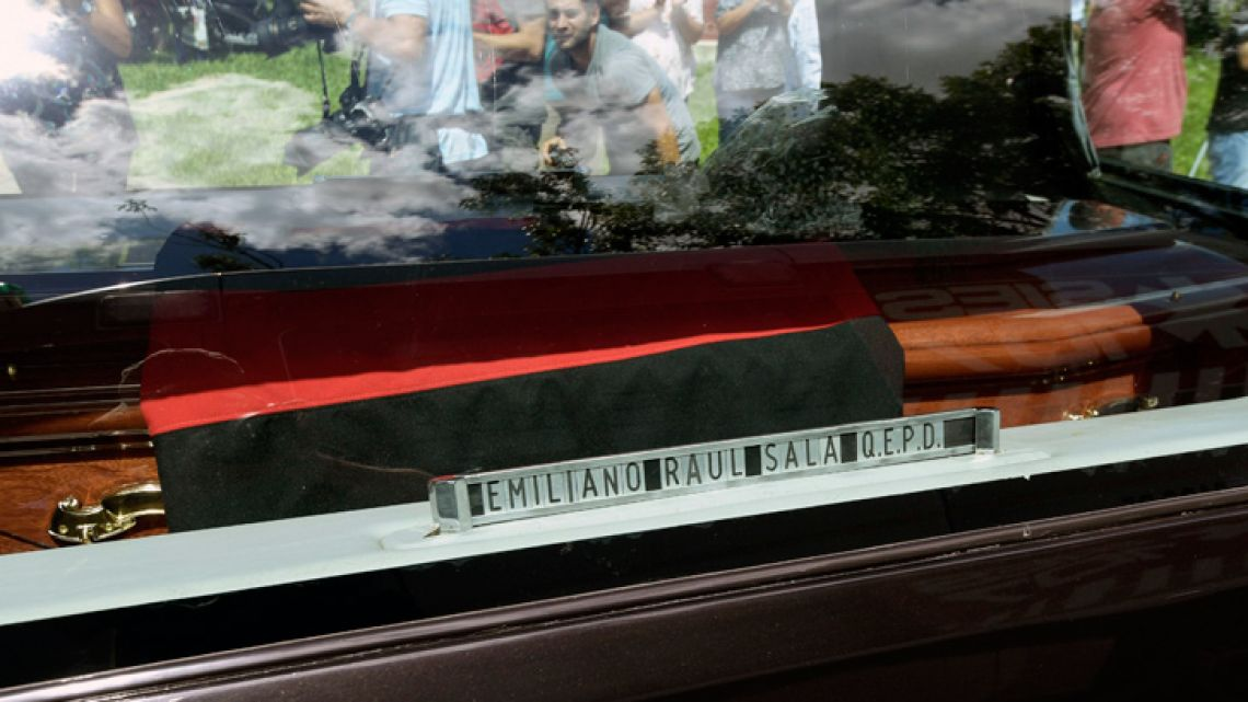 The coffin of late Argentine footballer Emiliano Sala drapped in the flag of his childhood's football club, the Club Atlético y Deportivo San Martín, is seen inside the hearse as it leaves the club's headquarters during his funeral service in Progreso, Santa Fe province on February 16, 2019.