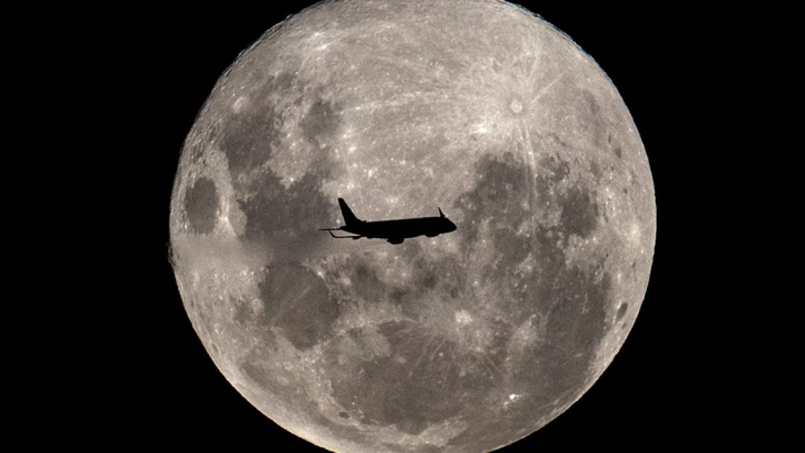 "An Embraer 190-100IGW plane (registration LV-CKZ) of Aerolineas Argentinas, on a regular flight from Buenos Aires to Bahía Blanca, passes in front of the ""Supermoon"" as seen from Buenos Aires on February 19, 2019."