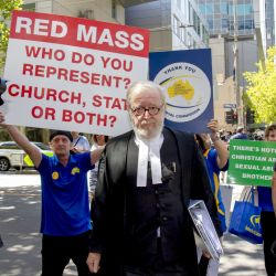 Cardinal George Pell's lawyer Robert Richter leaves the County Court as protesters hold placards in Melbourne, Australia, Wednesday, Feb. 27, 2019