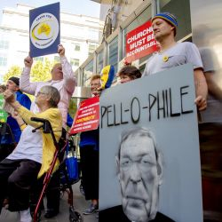 Protesters hold placards outside the County Court where Cardinal George Pell is to arrive in Melbourne, Australia, Wednesday, Feb. 27, 2019.