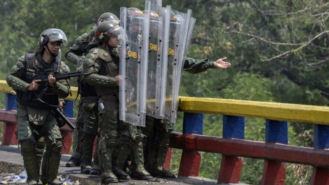 Members of Venezuela's Bolivarian National Guard protect themselves from demonstrators throwing stones from under the Francisco de Paula Santander international bridge in Urena, Venezuela, border with Colombia on February 24, 2019, following protests in the region after Venezuelan President Nicolas Maduro ordered a temporary close-down of the border with Colombia preventing the humanitarian aid to enter the country.