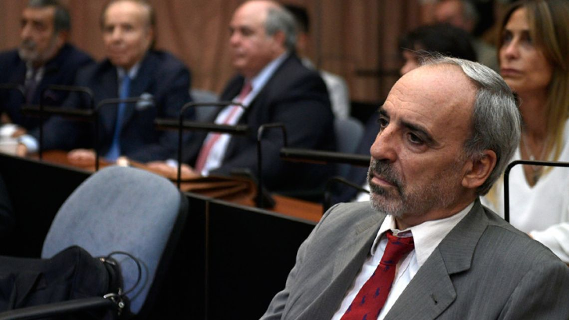 Former federal judge Juan José Galeano looks on before being found guilty during the AMIA bombing cover-up trial. Former president Carlos Menem can be seen out of focus in the background.