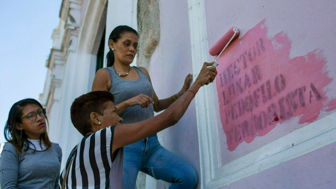 "In this Feb. 9, 2019 photo, faithful paint over graffiti that reads in Spanish: ""HECTOR LUNAR, PEDOPHILE, TERRORIST,"" on a wall of the Dulce Nombre de Jesus church, in the Petare slum of Caracas, Venezuela."