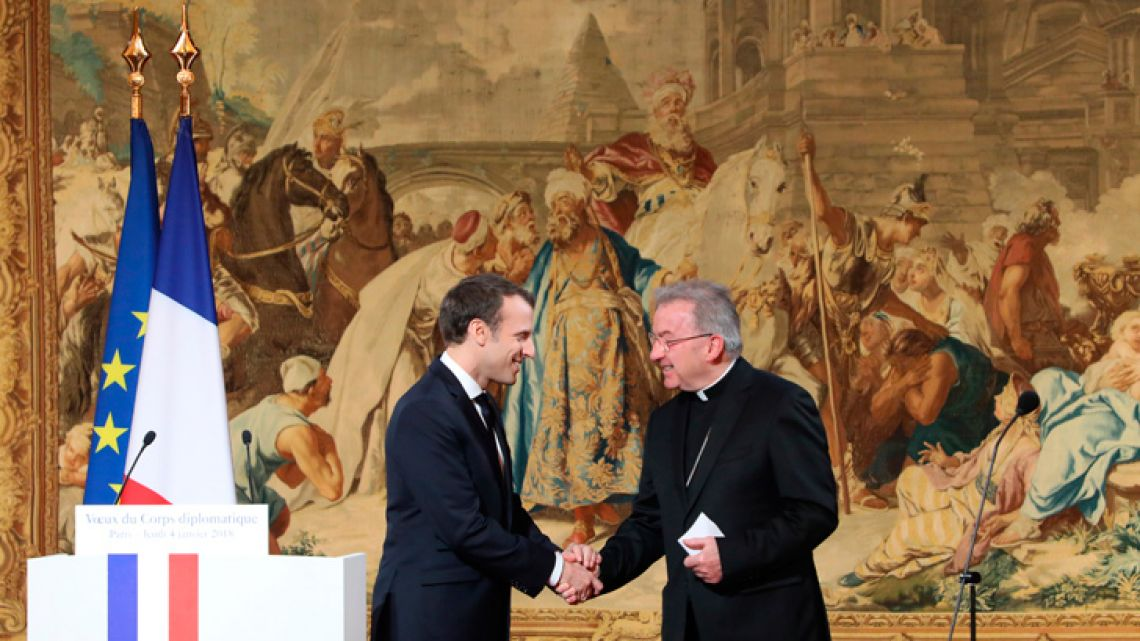 In this file photo taken on January 4, 2018, French President Emannuel Macron (left) shakes hands with Apostolic Nuncio to France, Luigi Ventura, during his New Year wishes to the diplomatic corps at the Élysée Palace in Paris.