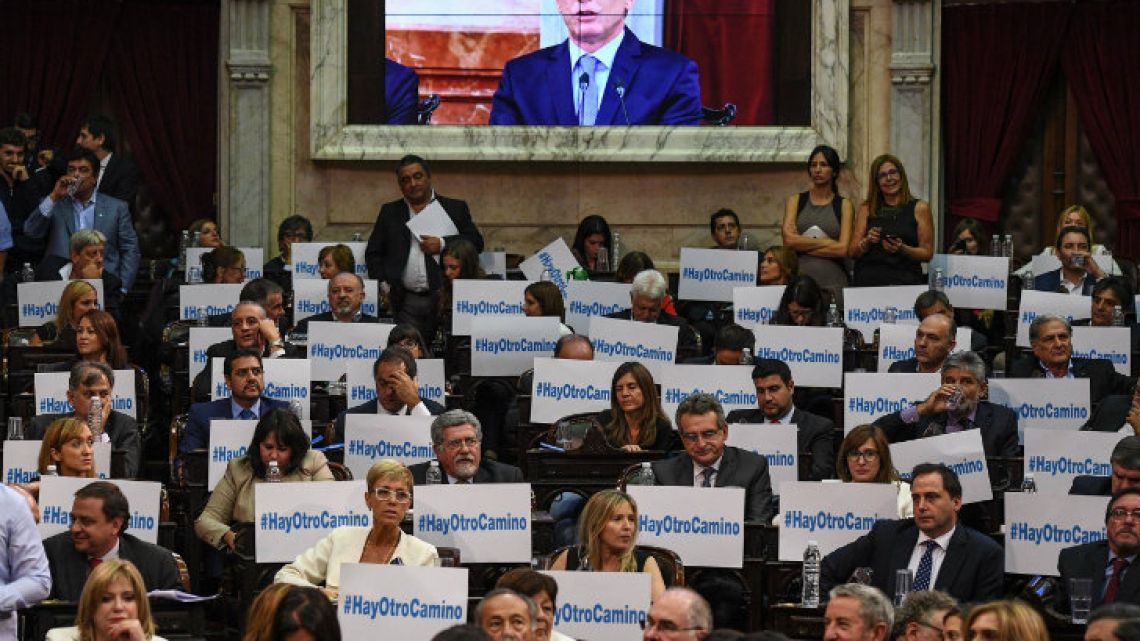 Opposition lawmakers listen to President Mauricio Macri's speech.