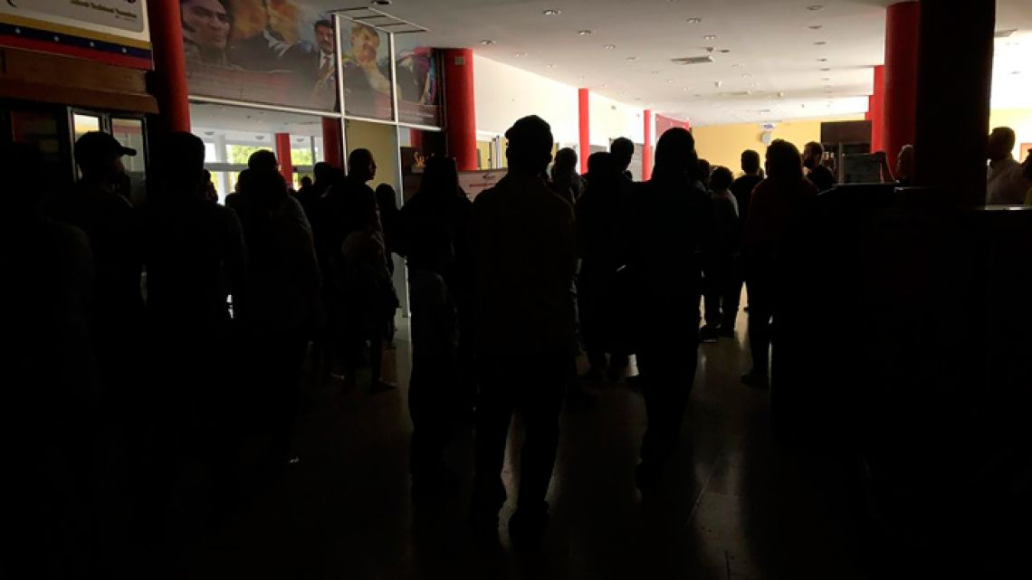 People remain at the airport in Barquisimeto, Venezuela on March 8, 2019, during a blackout. Venezuela's government suspended work and classes Friday due to a massive electricity blackout that has lasted for almost 16 hours and is affecting the majority of the country, the vice president said.